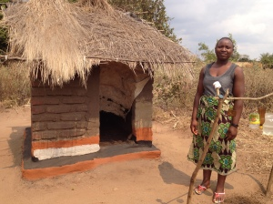 Woman standing outside a latrine in Malawi